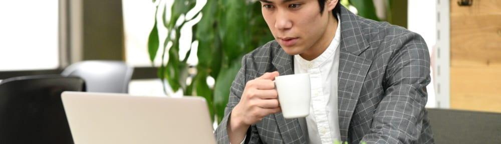 PCの前でコーヒーを飲む男性